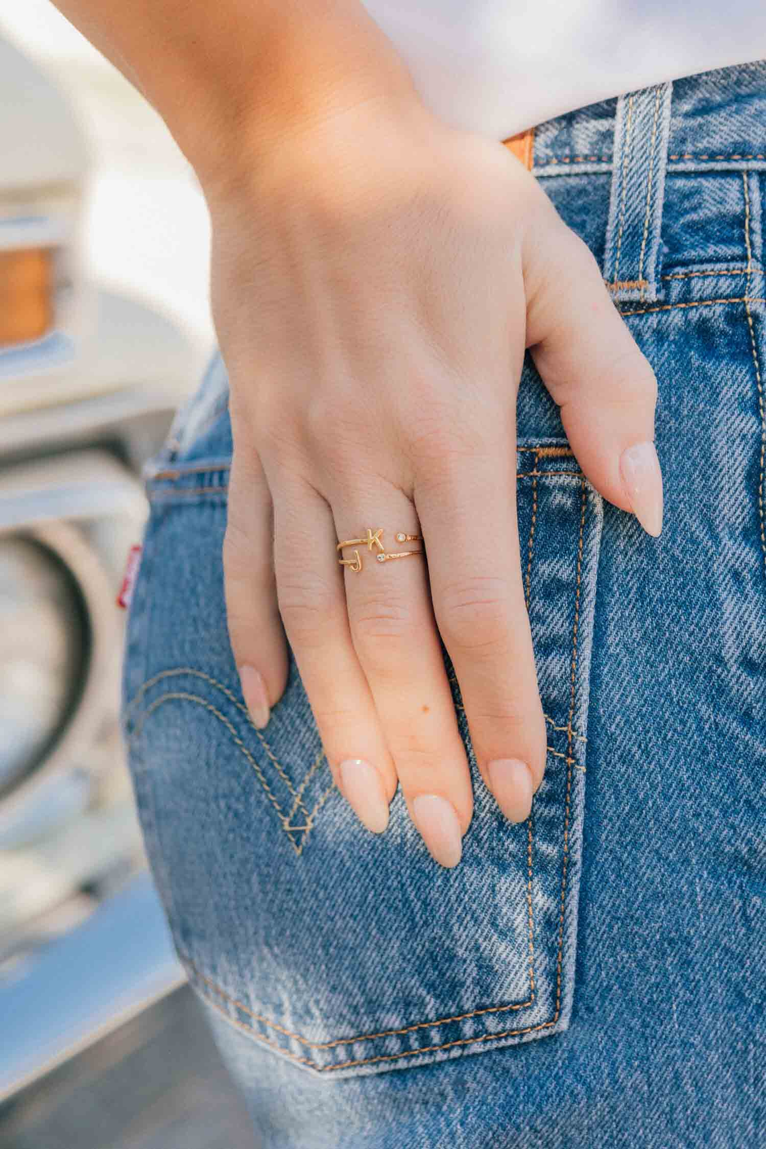 Woman's hand on jeans wearing Katie Dean Jewelry Initial Ring