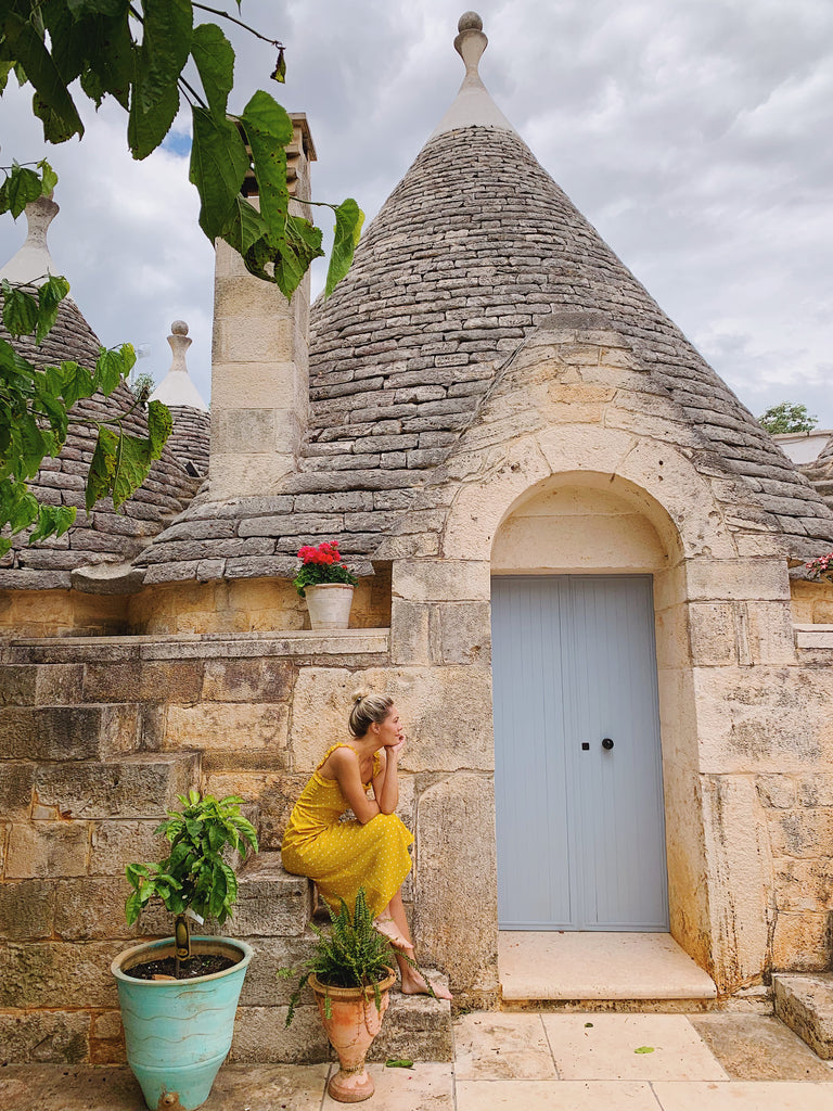 Katie Dean sitting on the steps of Trullo Sant'Angelo in a yellow dress