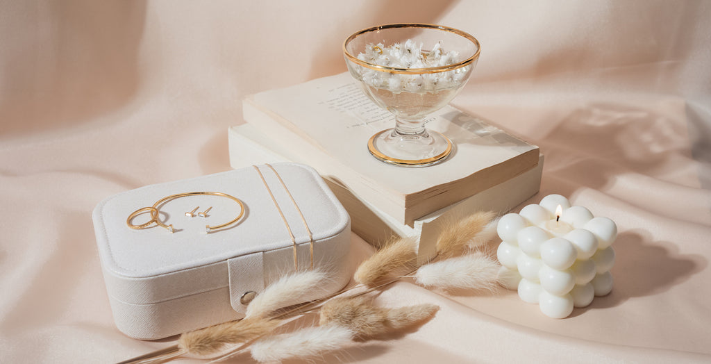Still life image showing a white jewelry case with dainty gold jewelry laying on top of it and to the right of it books stacked with a gold rimmed glass and a white bubble candle next to that