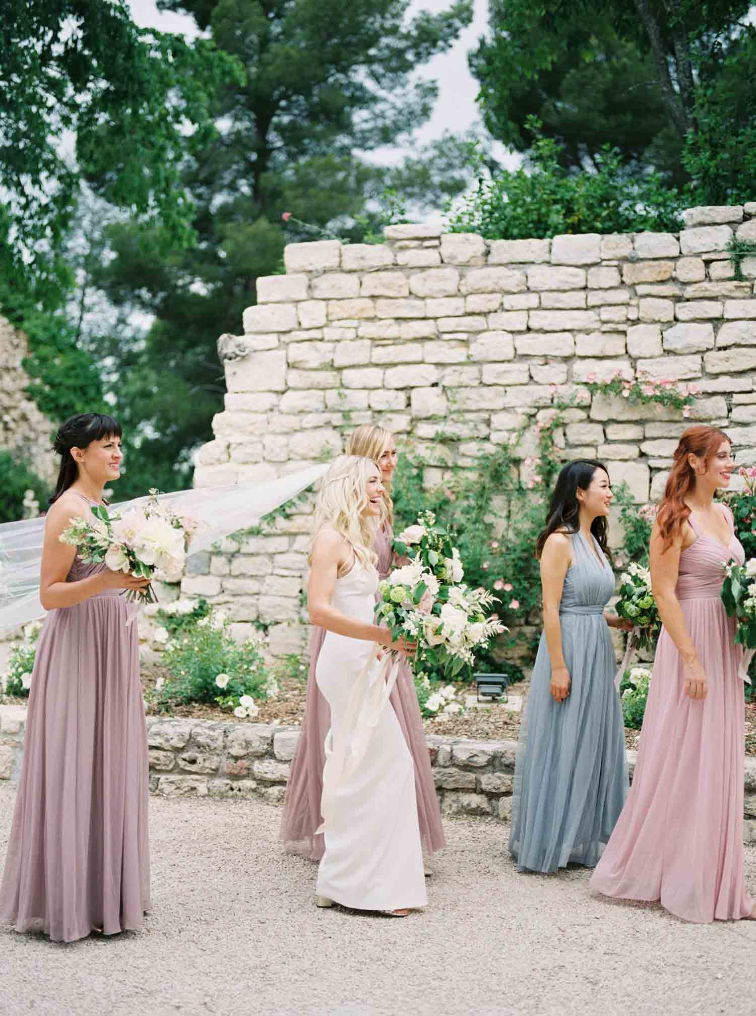 Bridesmaids walking outdoors with the bride.