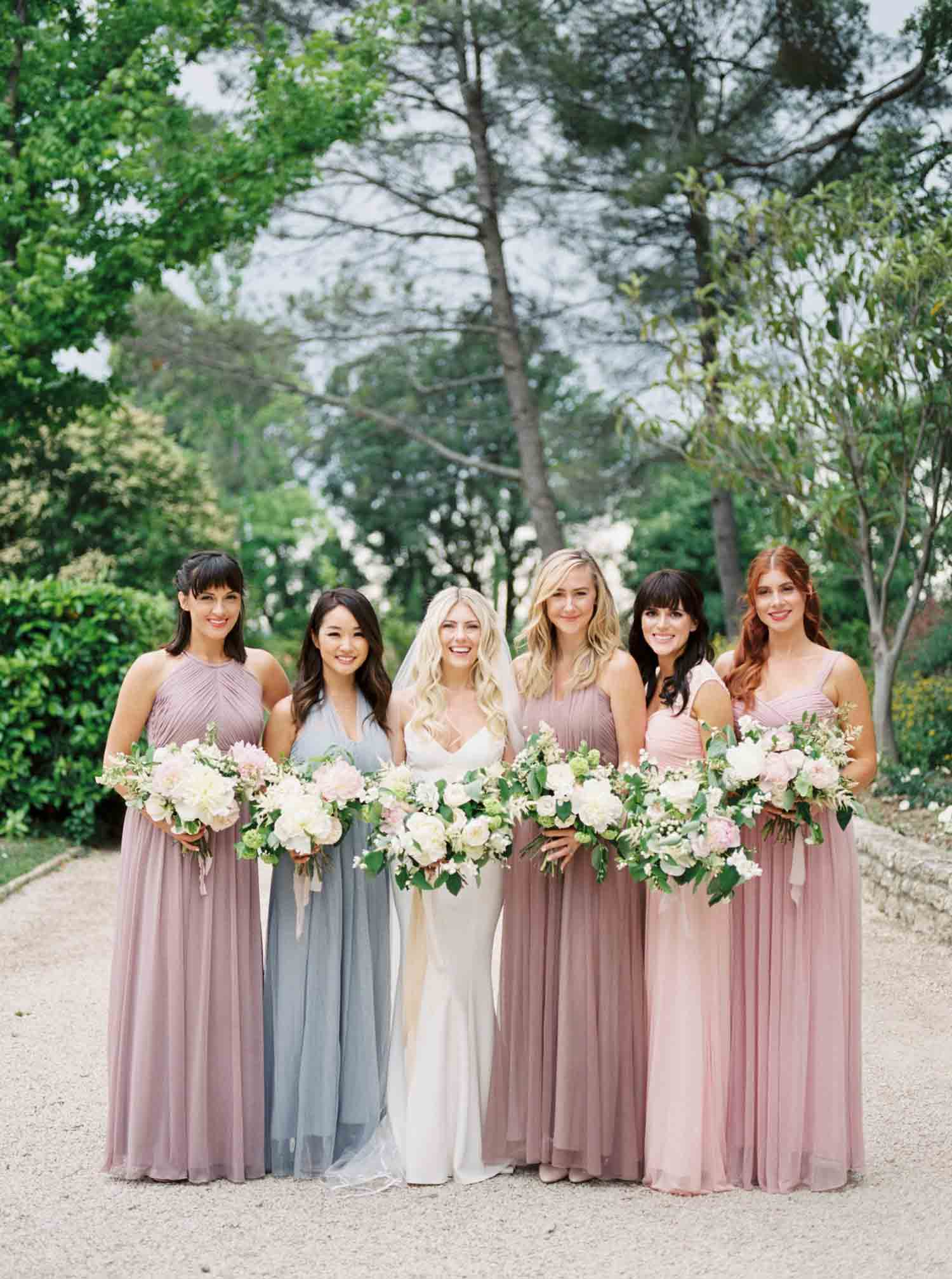 Bridesmaids standing in a row holding flowers next to the bride.