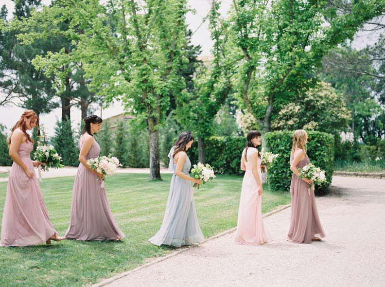 Five bridesmaids walking across green grass and driveway.