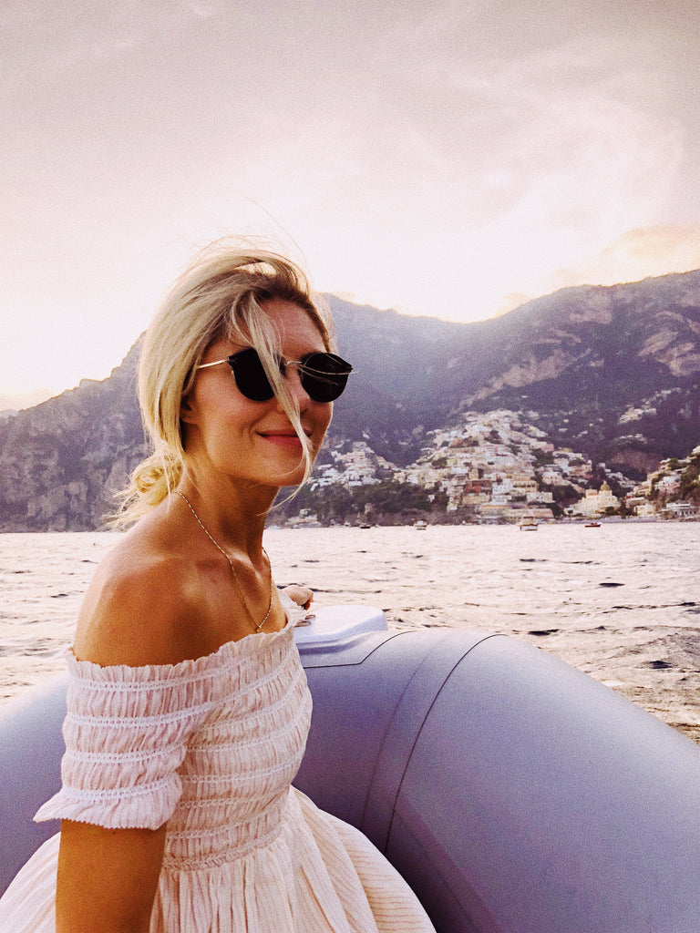 Katie Dean, on a boat with the Amalfi Coast in the background.