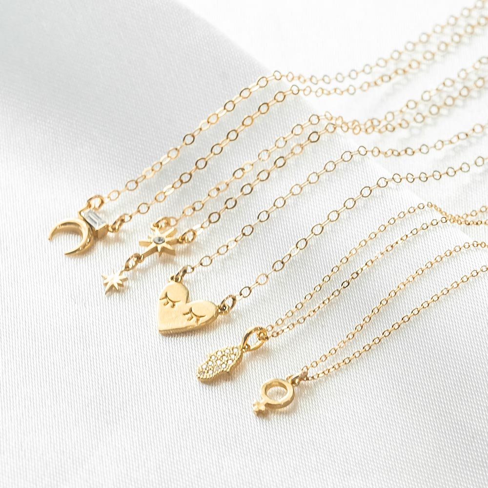 Katie Dean Jewelry dainty gold necklaces laying on a piece of white satin