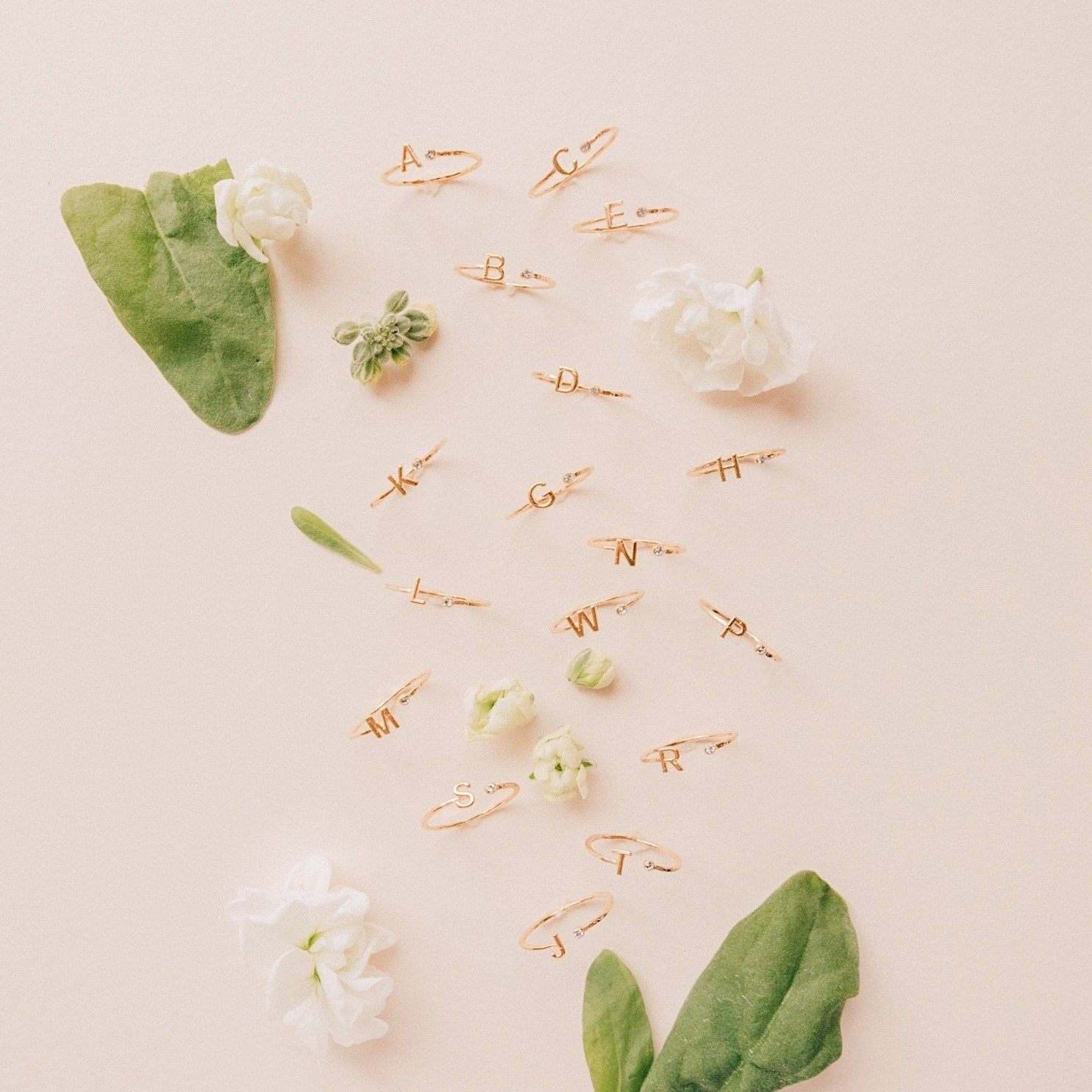 Gold dainty Initial Rings shown on a pink background with white flowers and green leaves
