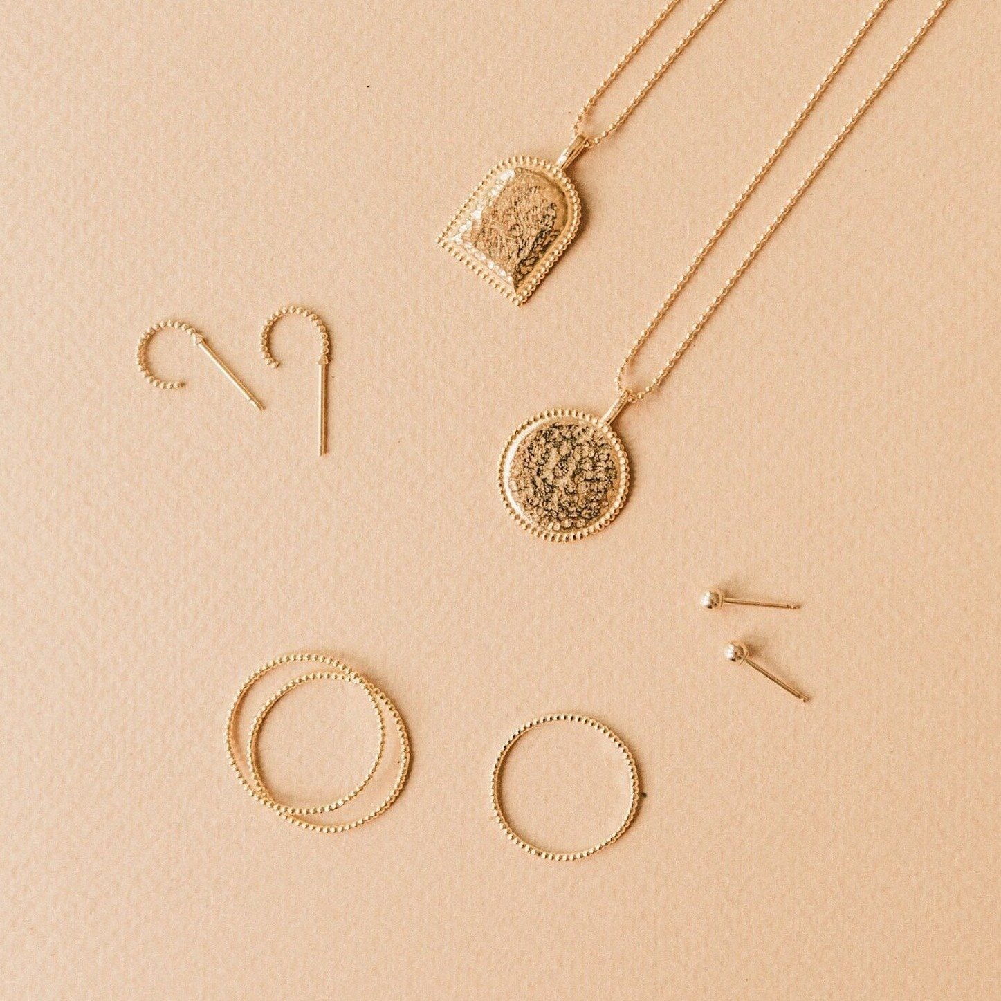 Beaded Coin Necklace, Beaded Arch Necklace, Beaded Rings and Beaded Hoop Earrings laying on a light brown background.