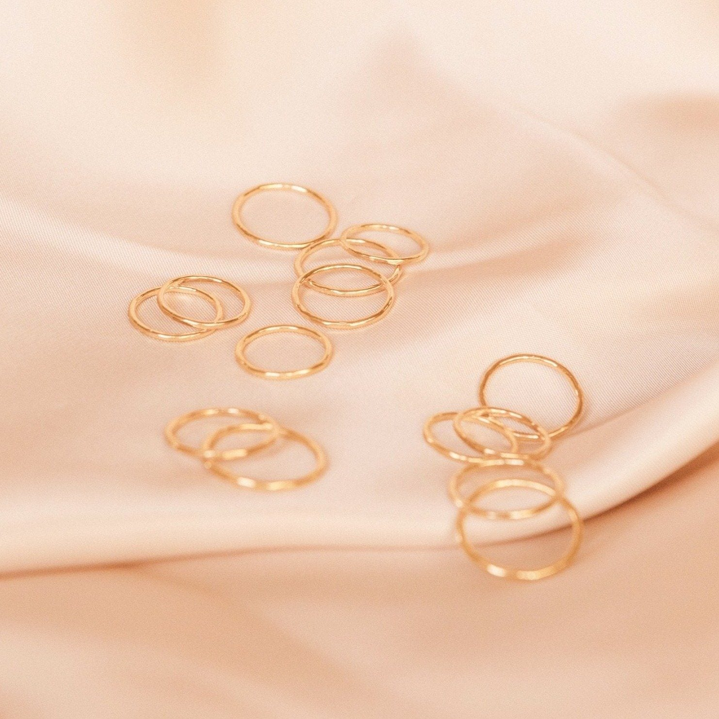 Dainty gold hammered band rings laid out on a piece of pink satin. Handmade by Katie Dean Jewelry in California.