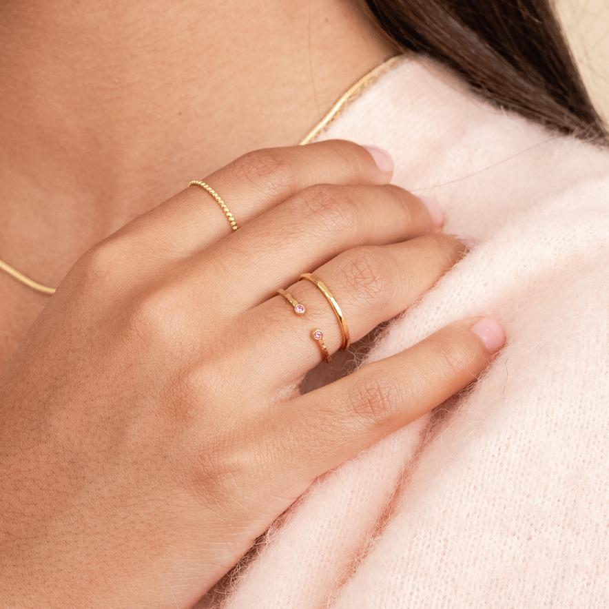 Model wearing the birthstone ring in October (rose) with a hammered band ring in gold stacked on top of it, made by Katie Dean Jewelry