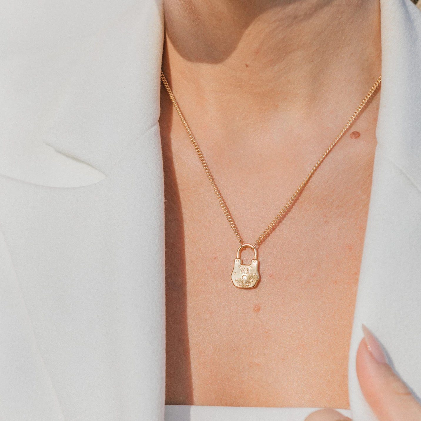 Image of model wearing the gold Love Lock Necklace with a white top.