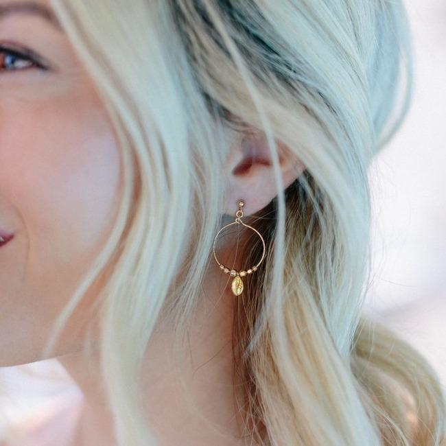 Puka Shell Hoop Earrings in gold on the ear of a girl looking to the left.