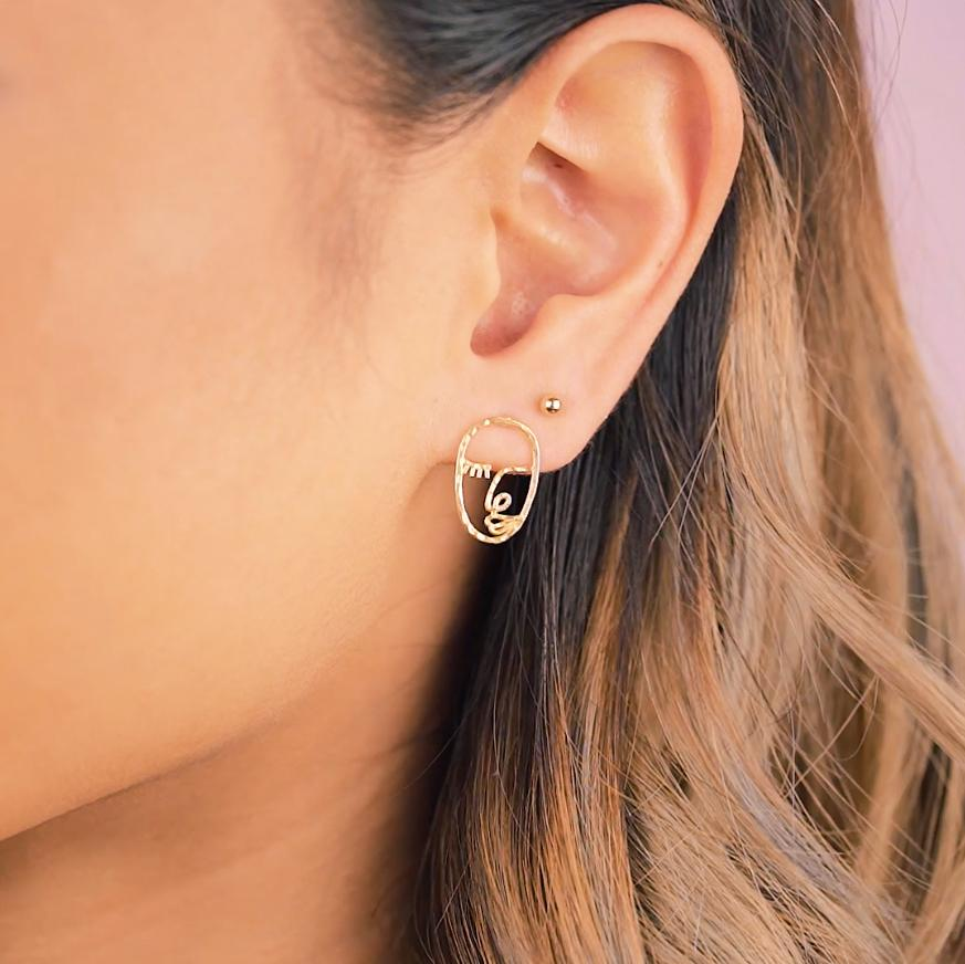 Model wearing the Beaded gold stud earring and the Artist Face Earring inspired by Matisse and Picasso. Handmade in California by Katie Dean Jewelry.