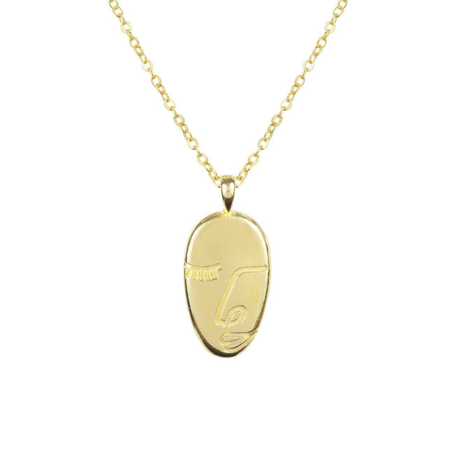 Gold and dainty Artist Face Necklace against a white background