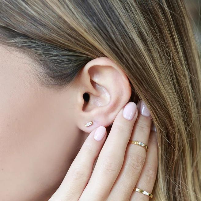 Katie Dean model holding hand below ear while wearing rings & the Baguette Studs.