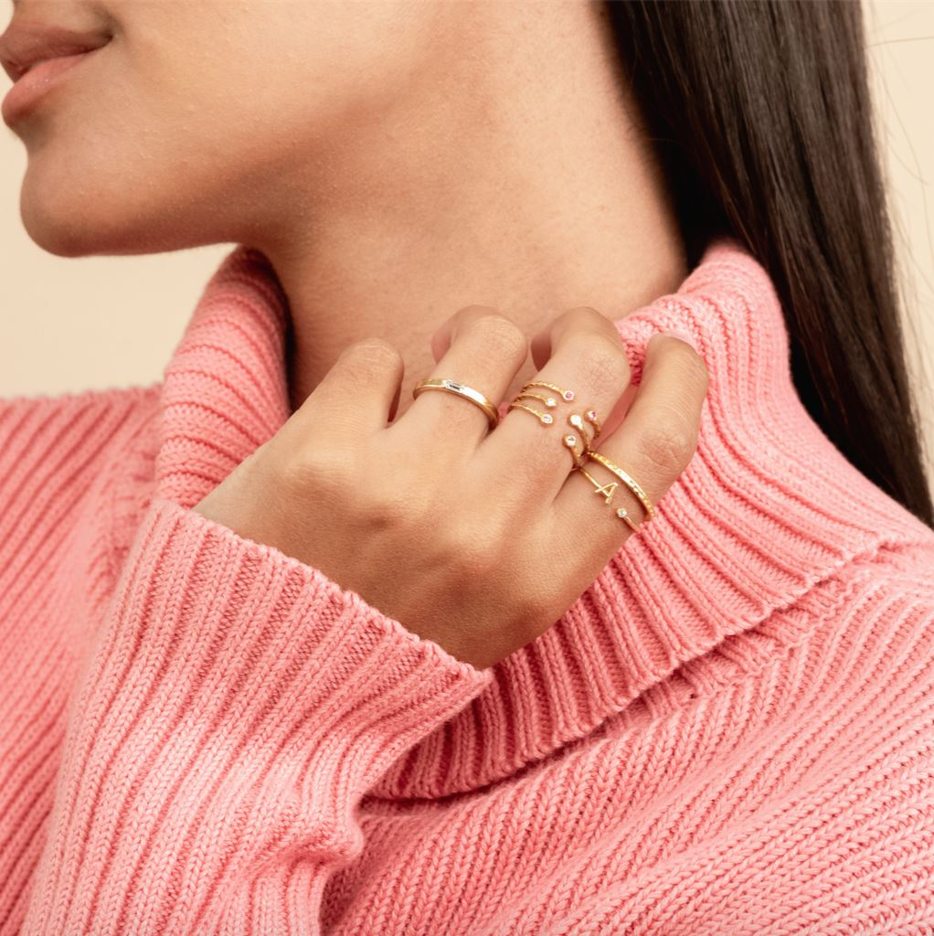 Model wearing the Initial Ring with other dainty gold stacking rings by Katie Dean Jewelry