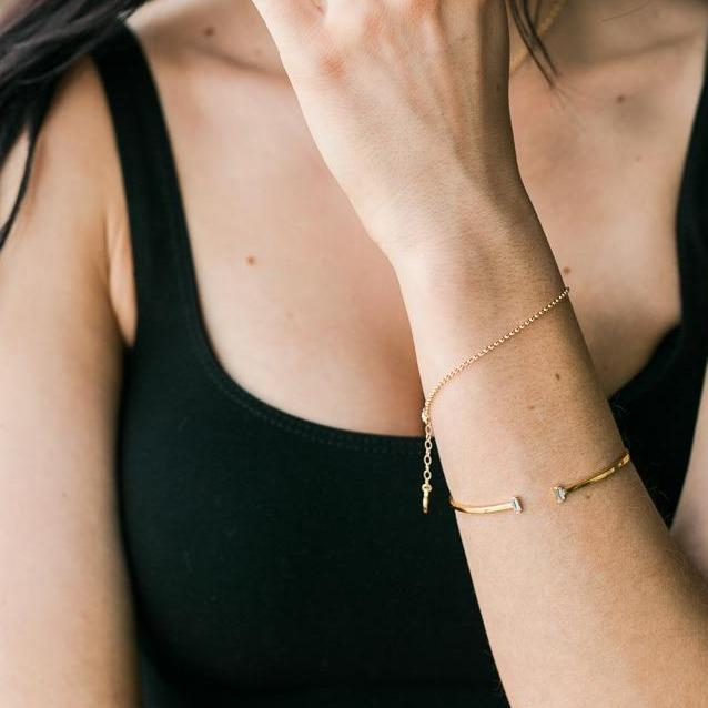 Picture of a model crossing her arm across the frame of the photo and wearing two dainty gold bracelets on her right wrist, one Evil Eye Bracelet and one Gold Rolo Bracelet, handmade by Katie Dean Jewelry