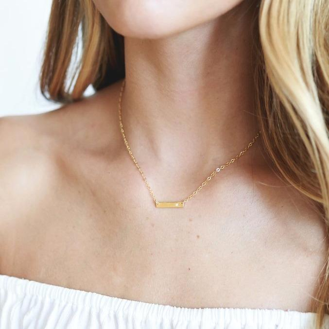 Dainty gold necklace with a bar charm about one inch long with a small white Swarovski crystal on the right side, on a model showing her chin, neck and torso.