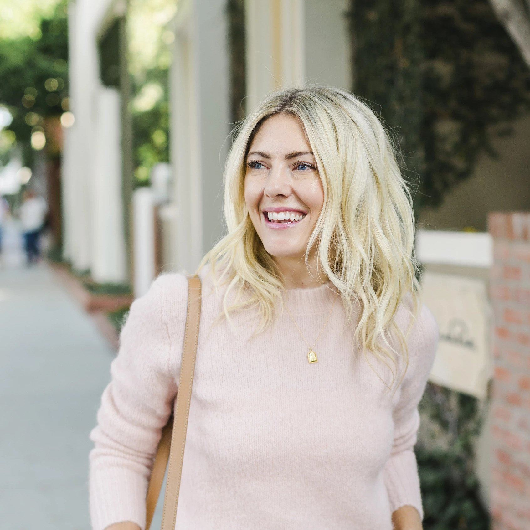 Katie Dean lifestyle shot of her wearing the Beaded Arch Necklace over a blush sweater.
