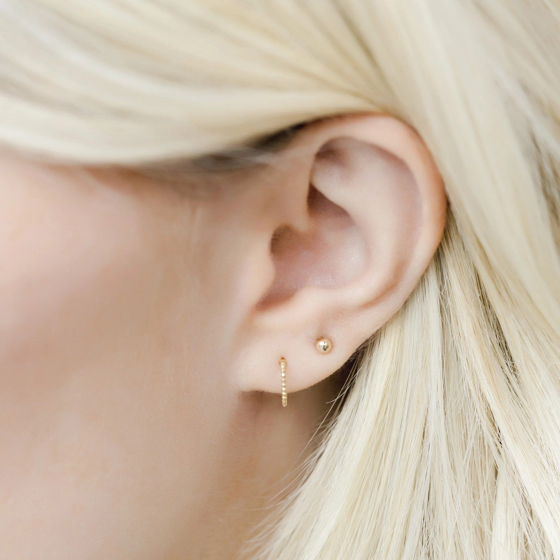 Up close image of models ear wearing the gold Beaded Hoop Studs.