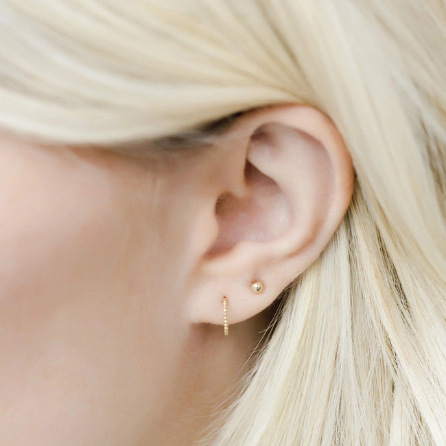 Up close image of models ear while wearing the gold Beaded Studs.