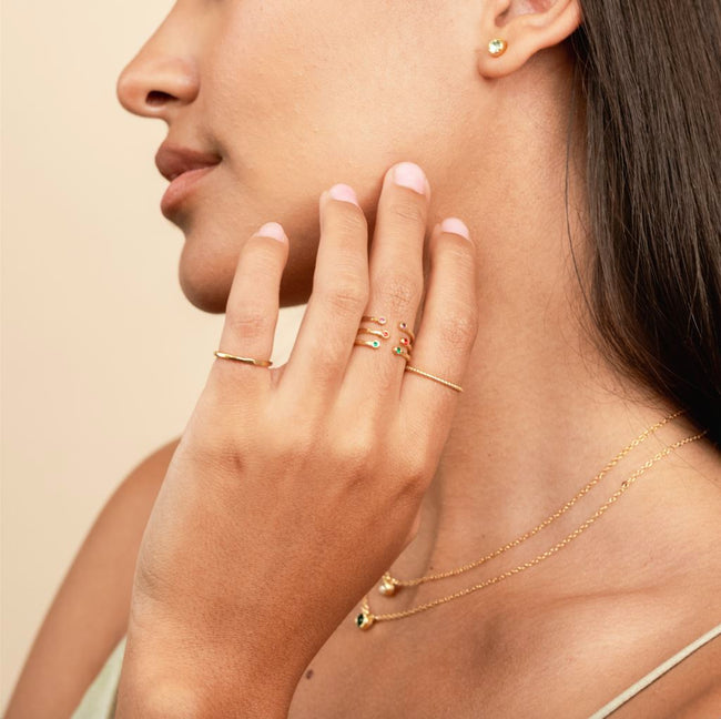Model with hand on her chin showing three birthstone rings stacked on the middle finger.