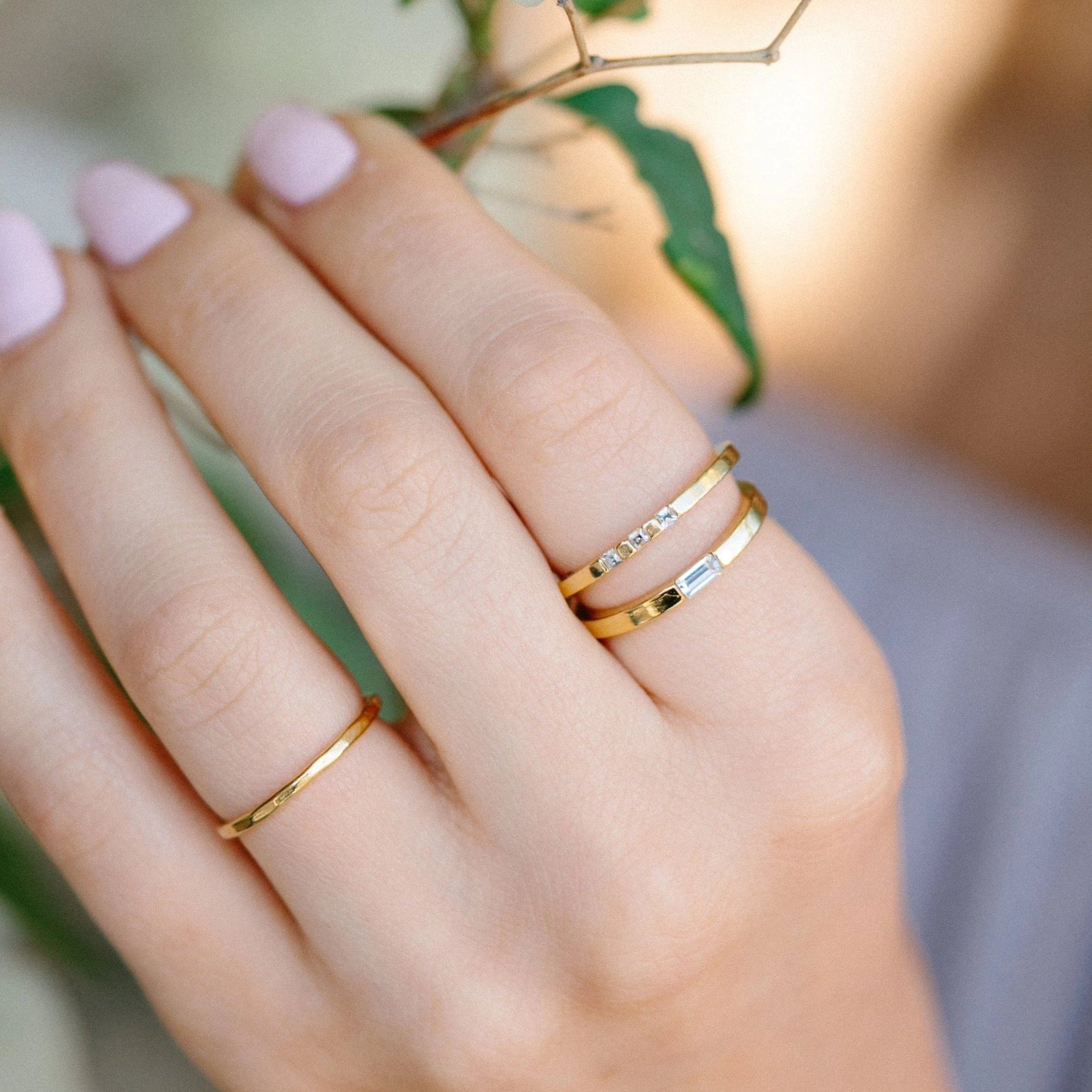 Up close image of models hand holding flowers & wearing Baguette ring.