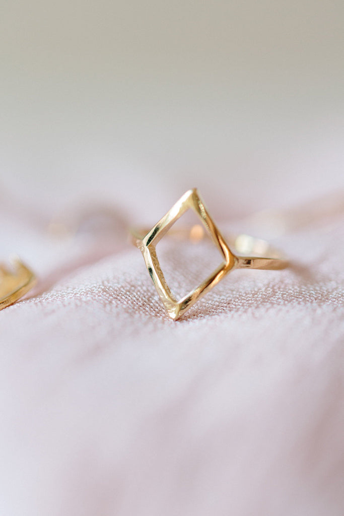 Up close image of gold Big Diamond Ring against blush fabric.