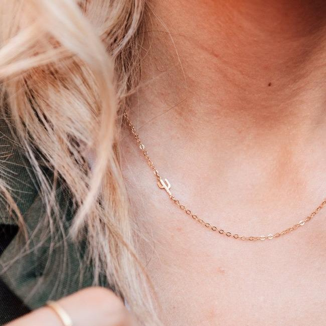 Dainty Gold Cactus Necklace with cactus charm sitting on the right side of the collar bone of the model.