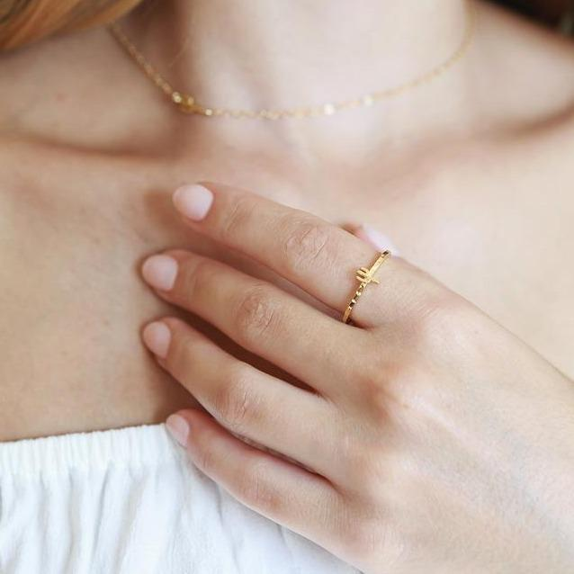 Model wearing the thin gold band ring with a small cactus charm on top of the band of the ring, in gold.