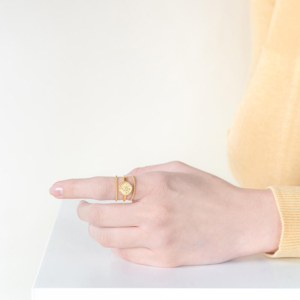 Models hand wearing the gold Celestial Stack against a white background while wearing a yellow top.