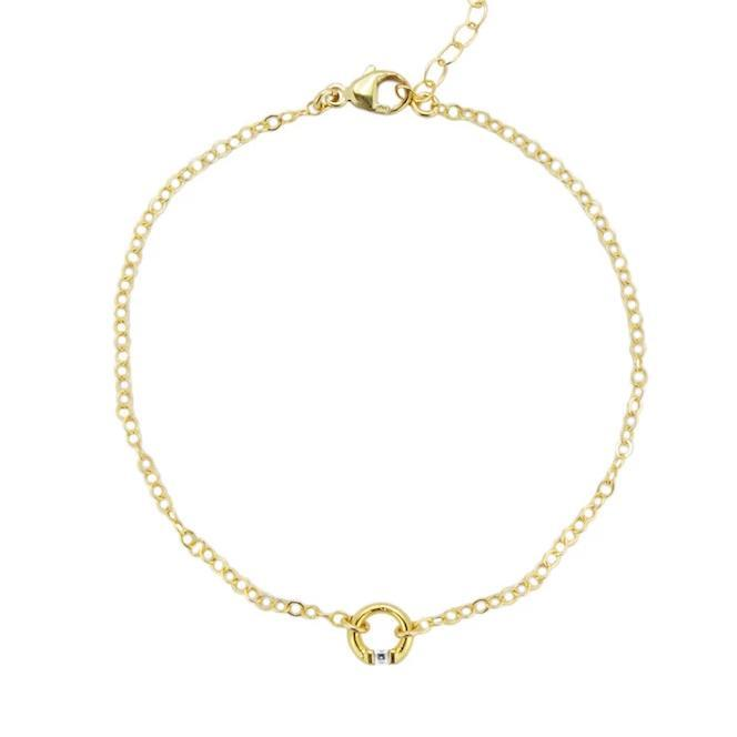 Up close image of the gold Circle Bracelet featuring a tiny circle charm in the middle against a white background.