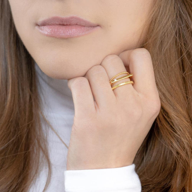 Model wearing the gold Classic Stack while holding hand to face.