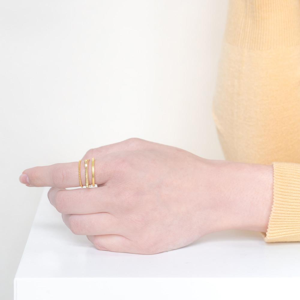 Up close image of models hand wearing the gold Classic Stack against a white background while wearing a yellow top.
