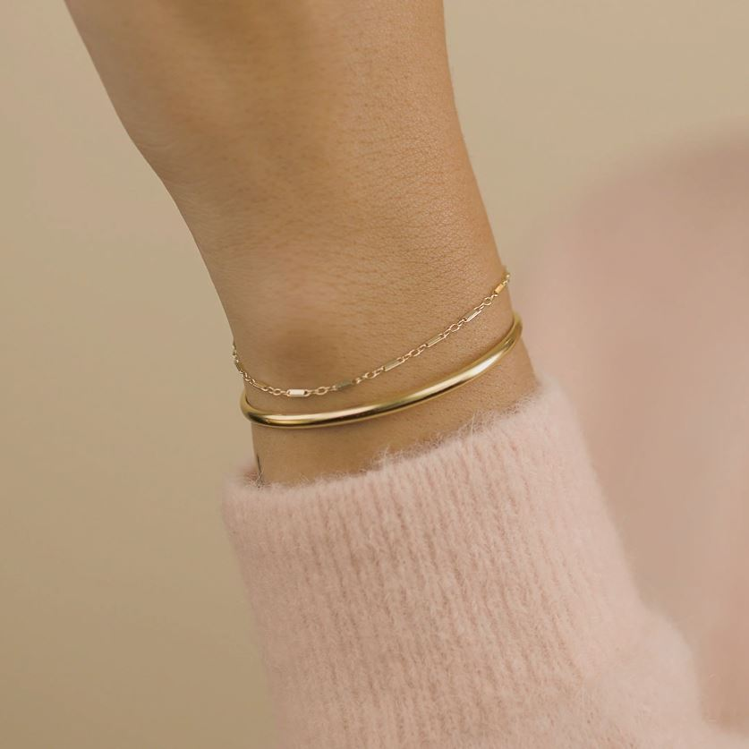 Hand model wearing the gold Claw Cuff and Linked Bracelet, made by Katie Dean Jewelry.