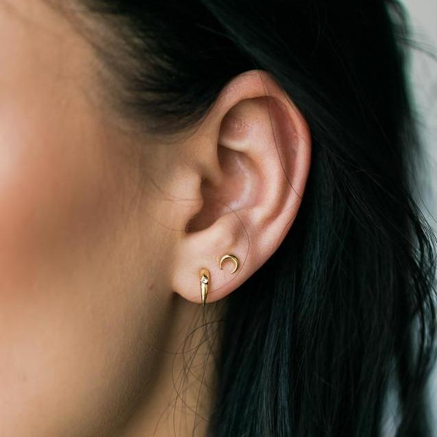 Gold crescent Moon Stud earrings on model with dark hair. Made by Katie Dean Jewelry.