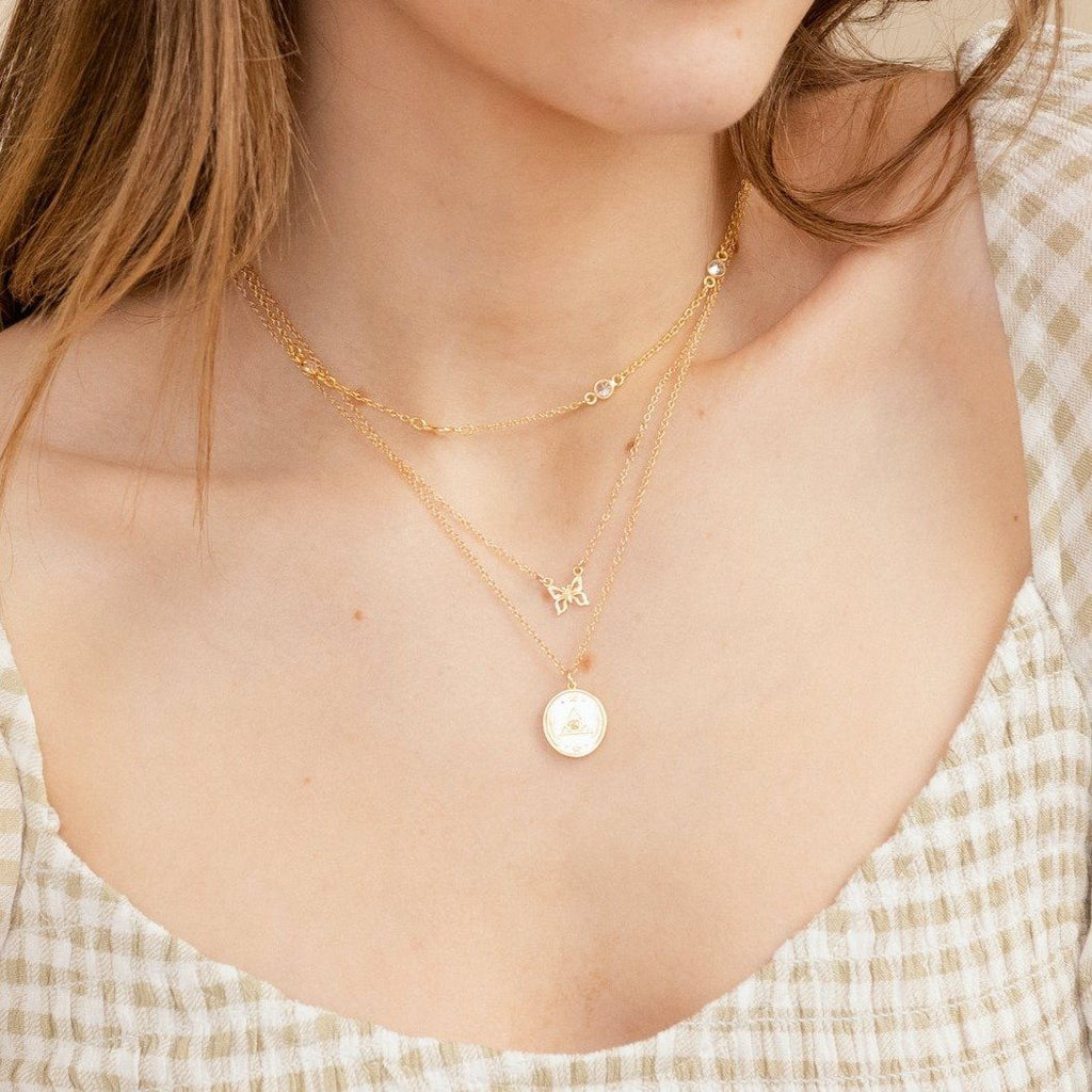 Model wearing a gold dainty necklace with round charm with an all seeing eye design, designed and made by Katie Dean Jewelry
