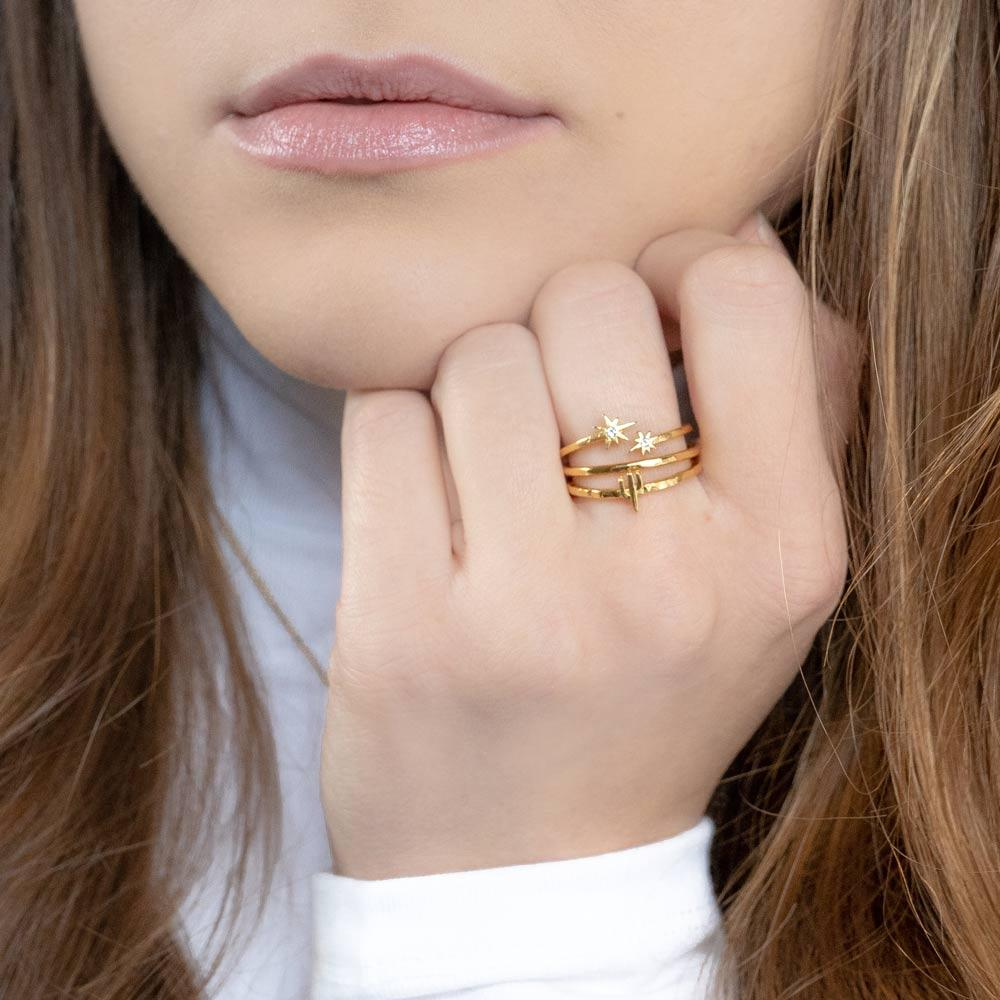 Katie Dean model wearing the gold Desert Stack while placing hand to face.
