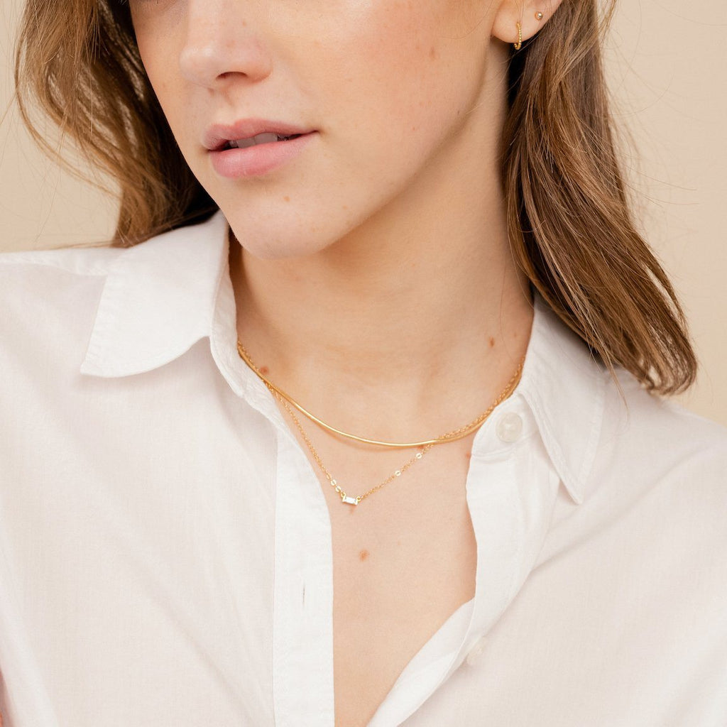 The dainty gold Elegant Necklace Set by Katie Dean Jewelry as seen on a model wearing a white button up collared shirt and dainty gold stud earrings