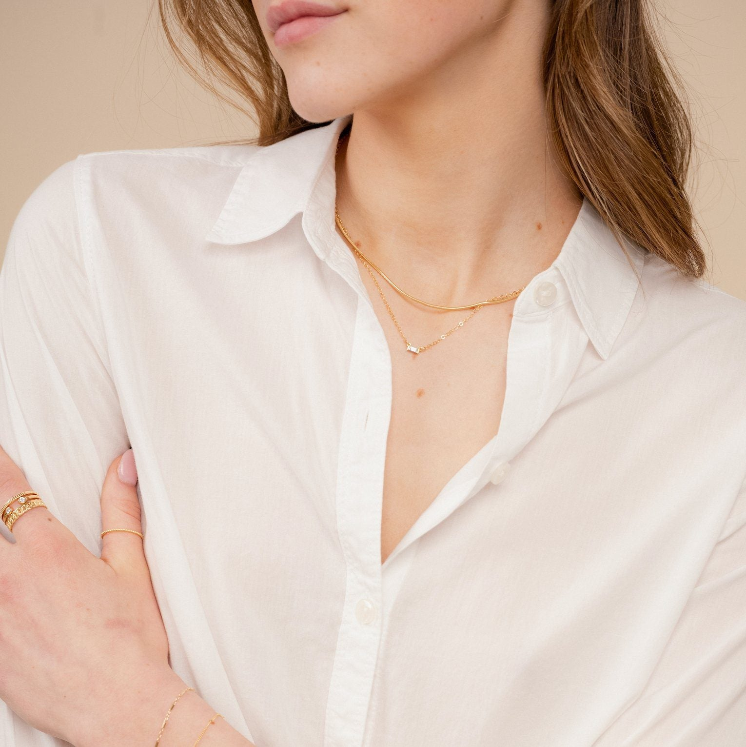 The dainty gold Elegant Necklace Set by Katie Dean Jewelry as seen on a model wearing a white button up collared shirt and dainty gold stacking rings.