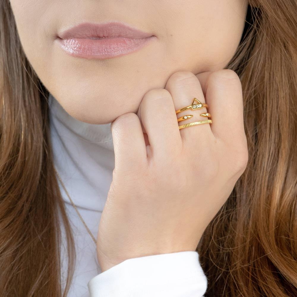Katie Dean model wearing the gold Essential Stack while placing hand to face.