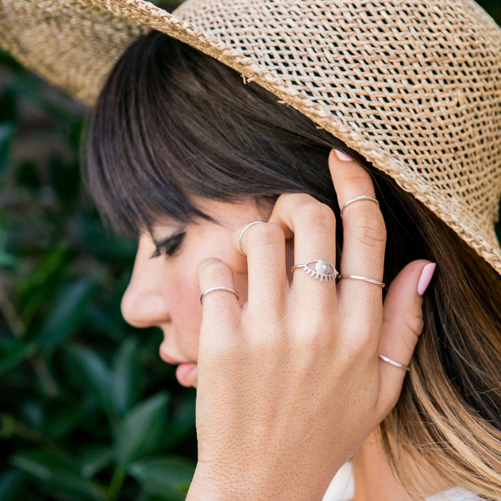 Katie Dean model wearing the silver Evil Eye Ring while wearing a tan hat.