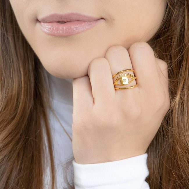 Model wearing the gold Evil Eye Stack while placing hand to face.