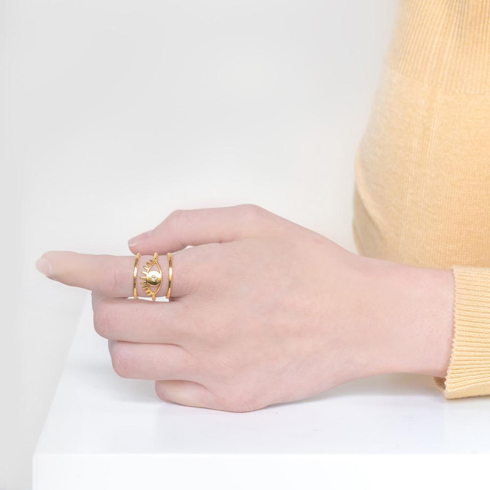 Image of models hand while wearing the gold Evil Eye Stack against a white background.