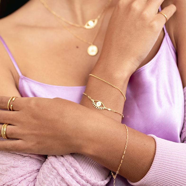 Picture of a model crossing her arms and wearing two dainty gold bracelets on her right wrist, one Evil Eye Bracelet and one Gold Rolo Bracelet, handmade by Katie Dean Jewelry