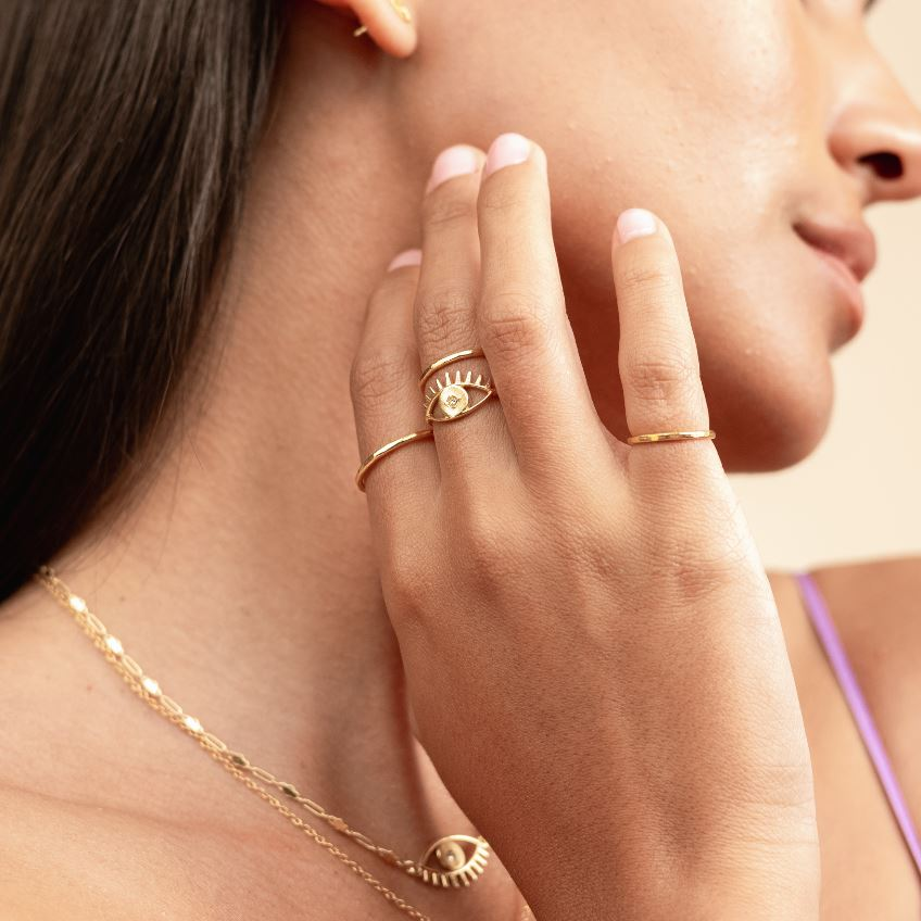 Picture of model with her hand reaching to her chin wearing four dainty gold rings, featuring the Evil Eye Ring Stack made by Katie Dean Jewelry.