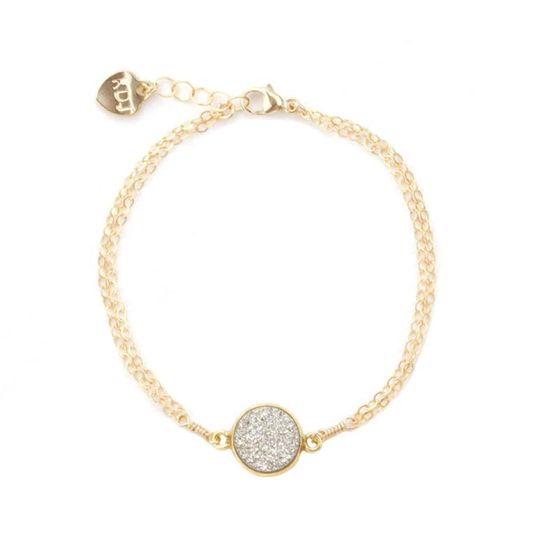 Up close image of the gold Fantasia Bracelet with a round silver stone.