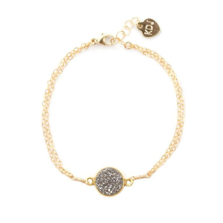 Up close image of the gold Fantasia Bracelet with a round dark gray stone.