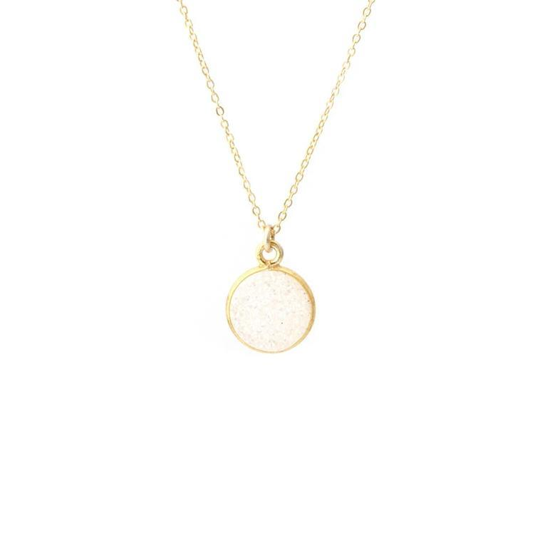 Up close image of the gold Fantasia Necklace with a white round stone.