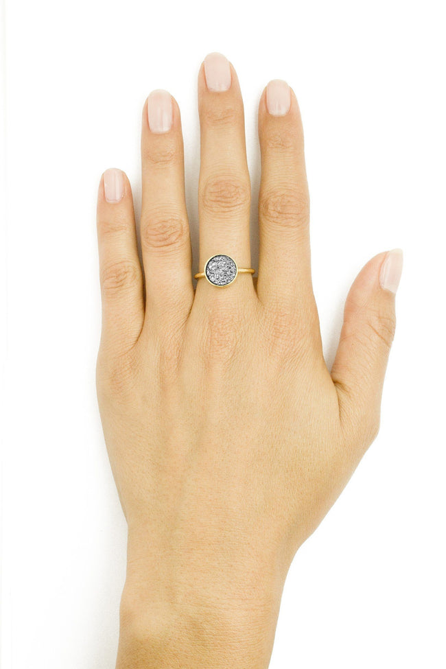 Image of models hand wearing the gold Fantasia Ring with a silver stone.