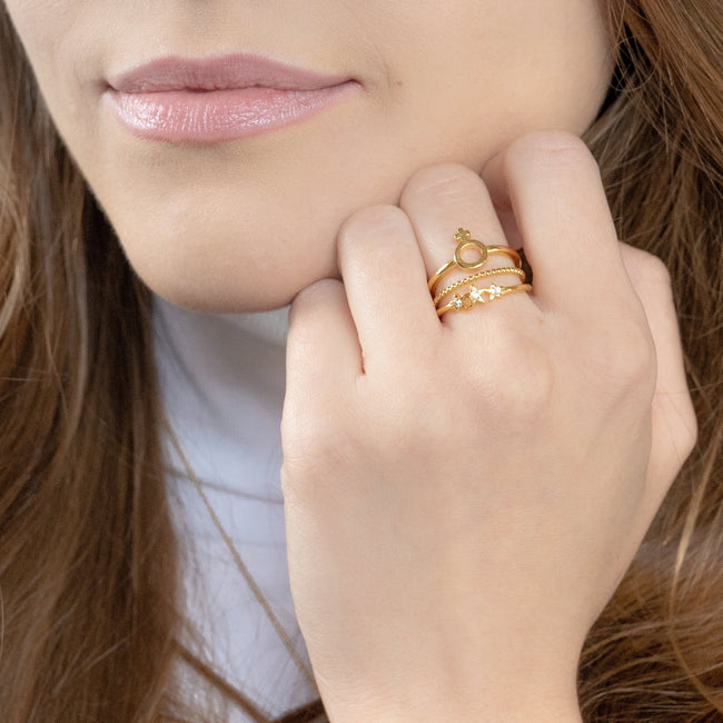 Image of model wearing the gold Feminist Stack while placing hand to face.