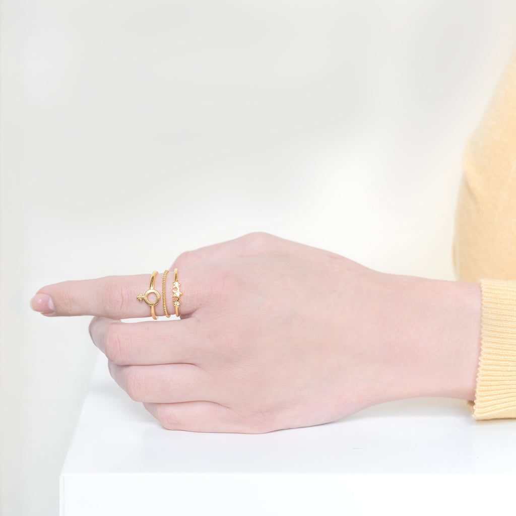 Image of models hand wearing the gold Feminist Stack against a white background.